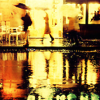 a group of people with their umbrellas reflected in the rain