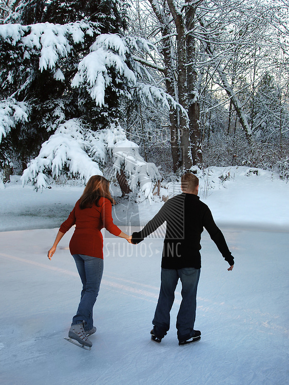 man and woman holding hands while skating in a winter wonderland
