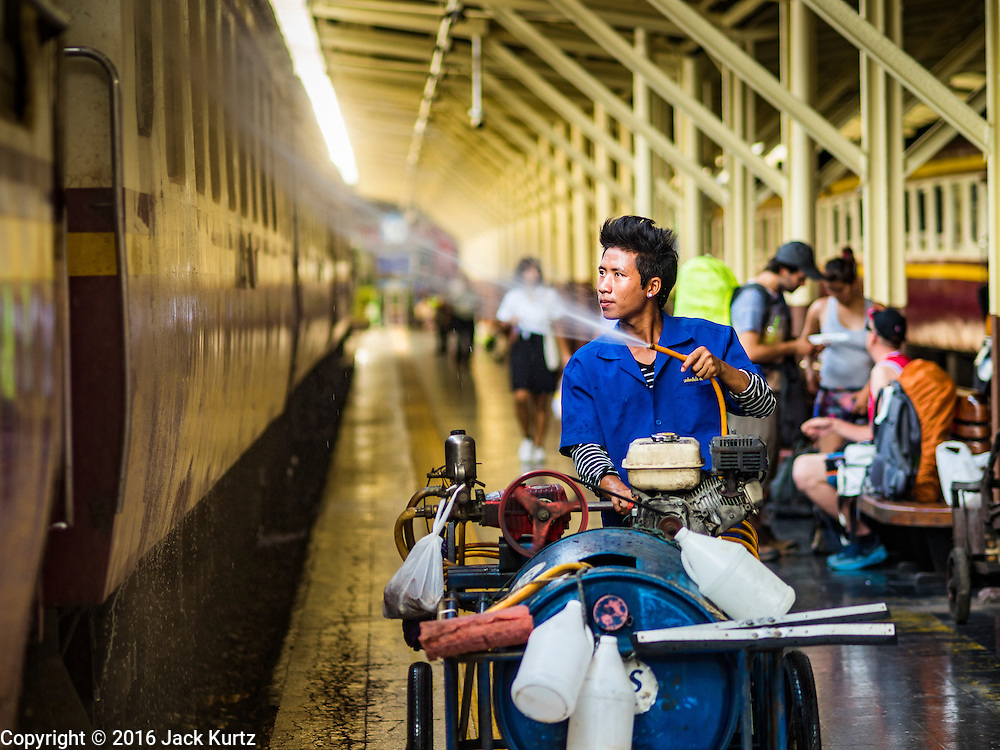 25 JUNE 2016 - BANGKOK, THAILAND:  A worker cleans the windows of a train in Hua Lamphong train station. The station opened on June 25, 1916 after six years' construction. The station was built in an Italian Neo-Renaissance-style, with decorated wooden roofs and stained glass windows. The architecture is attributed to Turin-born Mario Tamagno. There are 14 platforms, 26 ticket booths, and two electric display boards. Hua Lamphong serves over 130 trains and approximately 60,000 passengers each day. Since 2004 the station has been connected by an underground passage to the MRT (Metropolitan Rapid Transit) subway system's Hua Lamphong Station.     PHOTO BY JACK KURTZ
