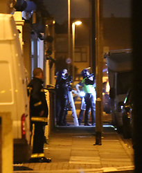 Portsmouth,Hampshire Sunday 30th October 2016 A man has been arrested after a four-hour rooftop stand-off  with Police in Portsmouth .<br /> <br /> Police were called out to Widley Road in the Stamshaw area of Portsmouth  at around 1am on Sunday morning.<br /> <br /> It is not yet clear why the man  was on the roof or what he has been arrested on suspicion of.<br /> <br /> Five police vehicles including armed response, two fire engines and two ambulance vehicles were called to the scene, which was cordoned off other surrounding road were made no go areas whilst Police dealt with the incident.<br /> <br /> At one point police considered breaking the stalemate by coaxing down the offender with the offer of a cigarette but only  giving him a light if he came down.<br /> <br /> The man could be seen  walked around the rooftops and shouted down abuse at officers in between throwing the roof slates. Just after 5am the man climbed down and was arrested.<br /> <br /> Two police officers and fire fighter narrowly escaped injuries  after a man began throwing roof  tiles during a stand-off.  During the four hour-long stand-off in which he threw tiles at the teams of officers who could be seen wearing riot gear and holding plastic shields the man was talked down by negotiators he was arrested by Police and then taken to QA hospital  for treatment.<br /> <br /> A Hampshire Police spokesman confirmed that they had been involved in the incident.<br /> <br /> One home owner who asked not to be named said &ldquo;I&rsquo;m sure it started about 1am. I can see it from my window. the bloke was running up and down the rooftops of the houses he is ripping whole tiles from the roofs and throwing them at Police.&rdquo;  <br /> <br /> The remains of the stand-off can be seen in the middle of the road  broken tiles that were lobbed at officers and others that have hit parked car causing Thousands  of pounds worth of damage to residents roofs and Parked vehicles. &copy;UKNIP With Video <br /> <br /> https://youtu.be/Ghv_HvDfcwU