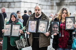 © Licensed to London News Pictures. 14/12/2017. London, UK. Family members of victims of the Grenfell fire hold up photographs of loved ones lost in the tragedy as they emerge from St Paul's Cathedral after attending the Grenfell Tower National Memorial Service. The service is attended by survivors and relatives of those who lost their lives in the fire, as well as members of the emergency services and members of the Royal family. 71 people were killed when a huge fire ripped though 24-storey Grenfell Tower block in west London in June 2017. Photo credit: Peter Macdiarmid/LNP