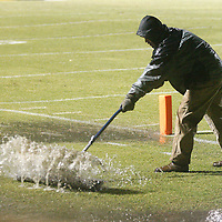 A man works to push water off of the football field during halftime of Friday night's game at Ripley.