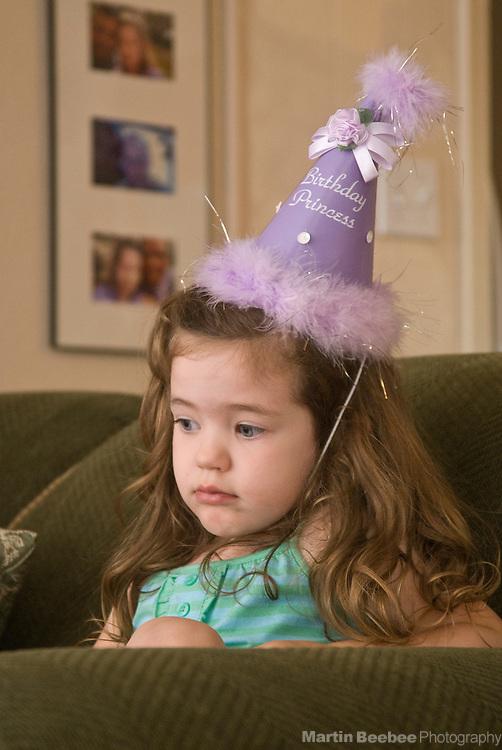 A toddler sulks on her third birthday