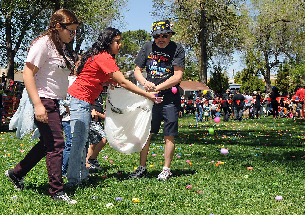 jt041517i/a sec/jim thompson/ left to right - Katrina Mann, Natalie Andrade and Eli Quintana spread the seeds of joy(plastic easter eggs)  at the Victory Outreach Albuquerque Church's HOPE Easter Egg Hunt and care Basket Giveaway at Roosevelt Park.  Saturday April 15, 2017. (Jim Thompson/Albuquerque Journal)