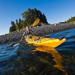 A man sea kayaking near the Porcupine Islands in Maine's Acadia National Park.  Frenchman Bay.  Bar Harbor. Rum Key.