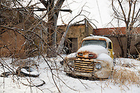 An old ford truck sits among the remains of tires and other autos in this long unused mechanics yard. This image was taken after a severe blizzard blew into North Texas and left much of the area covered with snow and ice.
