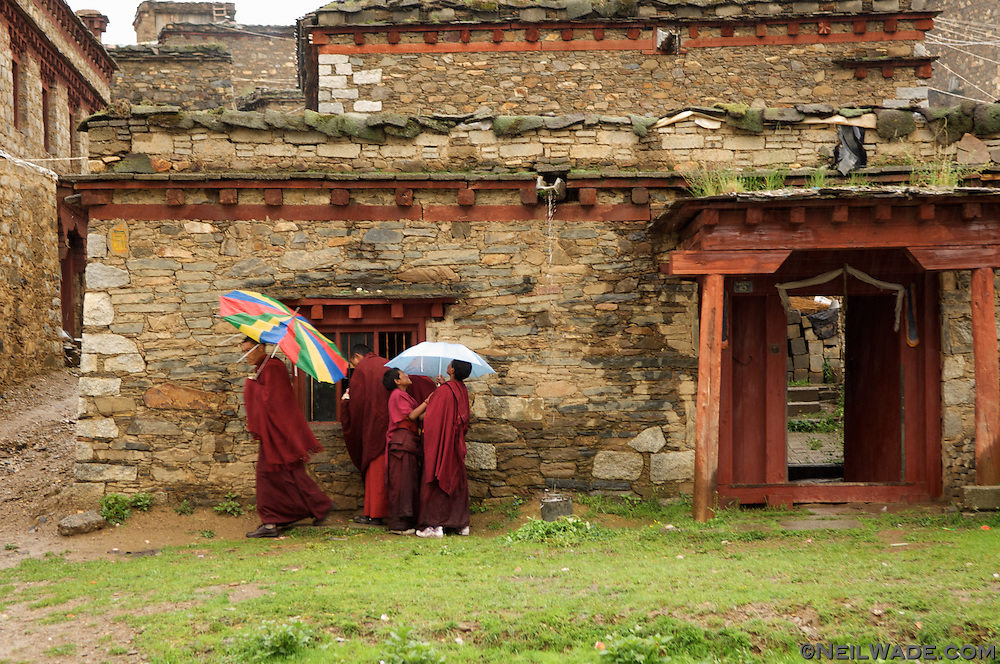 A group of novice Tibetan Buddhist monks buy candy from a store's window in a traditional Tibetan stone house in Litang, Tibet.