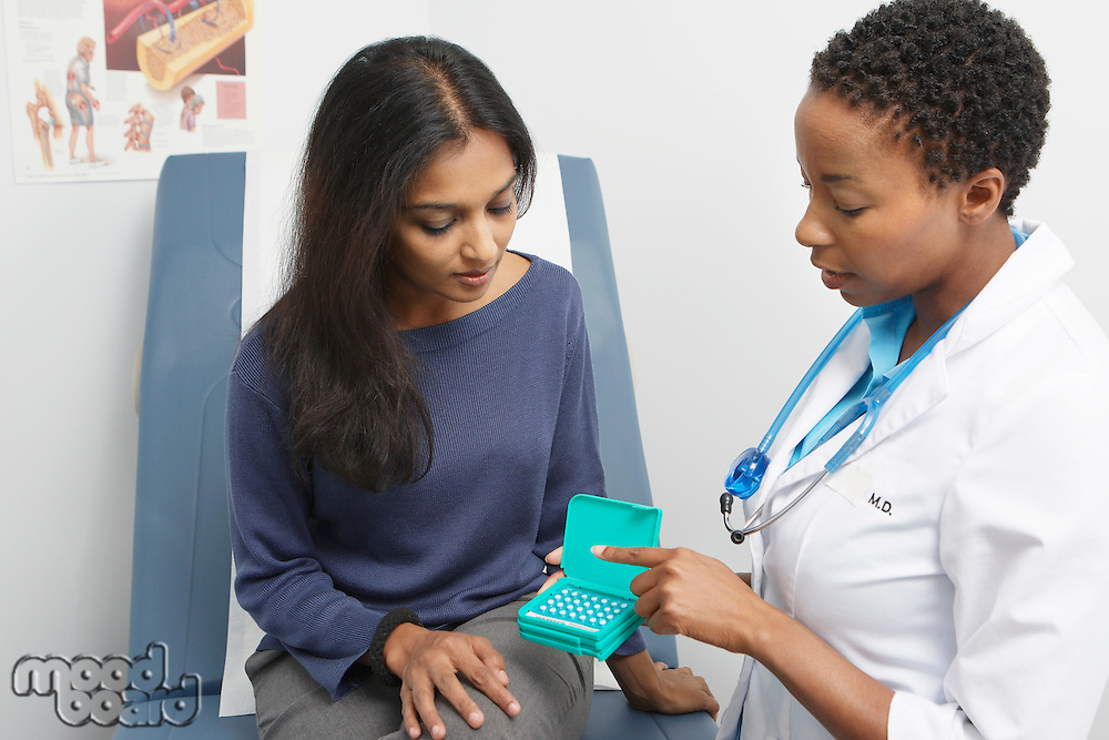 Female doctor passing medicine to patient