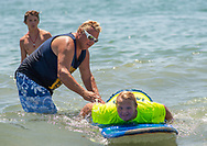 Chris Patro helps his son Brett Patro, 13, onto his paddle board during the 11th annual 21 Down Beach Day Monday, July 15, 2019 at Schellenger Street beach in Wildwood, New Jersey. Every summer, the Wildwood Beach Patrol opens Lincoln Ave Beach for kids with down syndrome and their families for 21 Down Beach Day. Often, kids with down syndrome aren't comfortable in the ocean. Their parents can't just relax and watch them frolic. But on July 15th, the kids swim with seasoned Wildwood lifeguards on soft-top paddle boards. (Photo by William Thomas Cain / CAIN IMAGES)