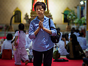 31 DECEMBER 2017 - BANGKOK, THAILAND: A woman walks in prayer before participating in an overnight meditation session on New Year's Eve at Wat Pathum Wanaram in central Bangkok. Many Thais go to temples and shrines to pray and meditate during New Year's Eve and New Year's Day.    PHOTO BY JACK KURTZ