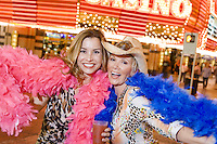 Two women wearing feather boas in front of casino building, portrait