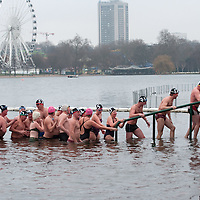 LONDON, ENGLAND - DECEMBER 25:  Members of the Serpentine Swimming Club exit the icy Serpentine waters after the annual Christmas Day Peter Pan Cup on December 25, 2009 in London, England.  The traditional 100 yards Christmas race got its name in 1904 after Sir James Barrie presented the first Peter Pan Cup and is only open to club members who have competed in at least three of the winter series races.   (Photo by Marco Secchi/Getty Images)
