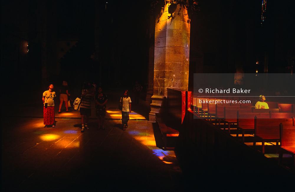 Stained glass light shines on to visitors, pillars and the floor of Palma's La Seu Cathedral in Mallorca.