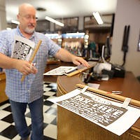 Johnny Rush, a sales clerk at Reed's on downtown Tupelo, gathers up the tax free sales signs as he works on putting them up throughout the store to prepare for the upcoming tax free shopping weekend. Items that qualify are Backpacks, T-Shirtsm Shoes, Jackets, Dresses and etc.