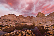 Stormy sunset over Isoscolese peak, Mt. Winchell, Thunderbolt Peak, and North Palisade peak from a lake in the Dusy Basin in the High Sierra mountain range in California.