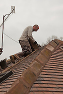 Roofer repointing ridge tiles...© Martin Jenkinson, tel 0114 258 6808 mobile 07831 189363 email martin@pressphotos.co.uk. Copyright Designs & Patents Act 1988, moral rights asserted credit required. No part of this photo to be stored, reproduced, manipulated or transmitted to third parties by any means without prior written permission
