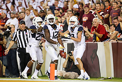 Sep 3, 2017; Landover, MD, USA; West Virginia Mountaineers wide receiver Gary Jennings (12) scores a touchdown and celebrates with West Virginia Mountaineers running back Justin Crawford (25) and West Virginia Mountaineers wide receiver David Sills V (13) during the fourth quarter against the Virginia Tech Hokies at FedEx Field. Mandatory Credit: Ben Queen-USA TODAY Sports