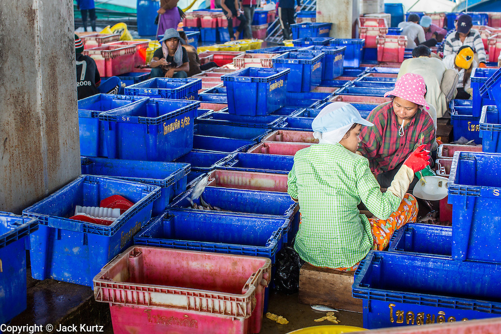 30 OCTOBER 2012 - PATTANI, PATTANI, THAILAND:  Immigrant workers in the Thai fishing port of Pattani. Thailand's fishing industry relies on immigrant workers, mostly from Myanmar but also Laos and Cambodia. There have been allegations of worker abuse, including charges that workers are held in slave labor like conditions. There are hundreds of thousands of immigrant workers in the Thai fishing industry. Most are from Myanmar (Burma) but there are also Cambodian and Laotian workers in the industry.    PHOTO BY JACK KURTZ