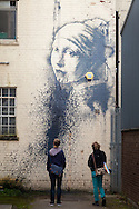 © Rob Arnold.  22/10/2014. Avon, UK. People visiting the new work by Banksy, 'Girl with a Pierced Eardrum', on Hanover Place in Bristol, which has been defaced within hours of appearing.. Photo credit : Rob Arnold