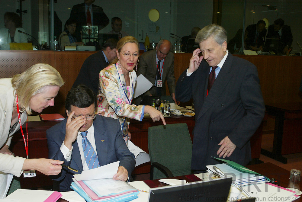 BRUSSELS - BELGIUM - 16 JUNE 2006 -- EU SUMMIT -- From left The President of the European Commission Jose Manuel BARROSO gets help from an aide while  Jean-Claude TRICHET (R) the President of the European Central Bank (ECB) speaks with Benita FERRERO-WALDNER, EU Commissioner PHOTO: ERIK LUNTANG /