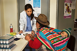 "Abby Wong, a student at the Medical College of Georgia, takes information from a Peruvian mother and child during outreach by CerviCusco, a nonprofit organization dedicated to reducing the spread of cervical cancer in Peruvian women, who have one of the highest rates of cervical cancer in the world. This is disproportionately true for women who live in the isolated mountain regions of the country. Healthcare workers like Wong typically go door-to-door in villages like this one, encouraging women to come to the clinic to receive pap smears. Wong said her Spanish is minimal. ""I do a lot of charades and smile a lot."""
