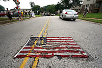 A partially burned American flag lies on the street near the spot where Michael Brown was killed before an event to mark the one year anniversary of the killing of Michael Brown Jr. in Ferguson, Missouri August 9, 2015.  Several hundred people gathered in Ferguson, Missouri, on Sunday to mark the one-year anniversary of the shooting death of an unarmed black teenager by a white police officer that sparked protests and a national debate on race and justice.  REUTERS/Rick Wilking