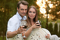 Portrait of young couple having red wine on chairs in park