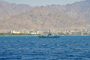 Israel, Eilat, Israeli navy Dabur class patrol boat in the Red Sea. Aqaba, Jordan in the background