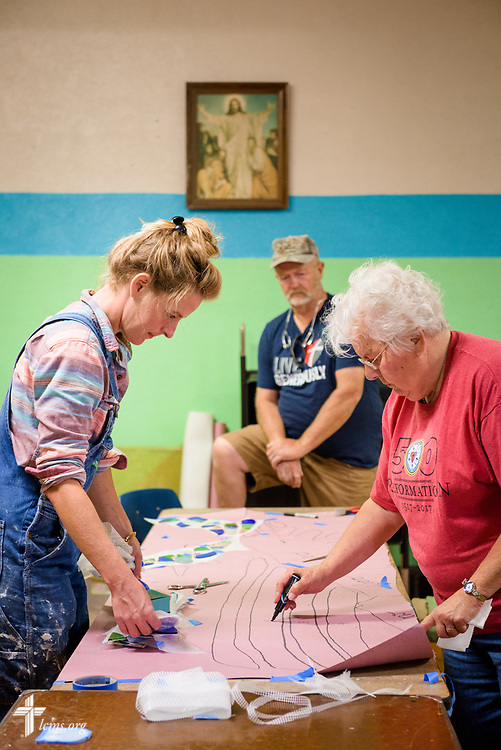 Artist Rachel Ziegler works on her mural project commemorating the 500th anniversary of the Lutheran Reformation with Marilyn Bader and Tim Morthole at Zion Lutheran Church, Worms, Neb., on Saturday, Sept. 23, 2017. LCMS Communications/Erik M. Lunsford