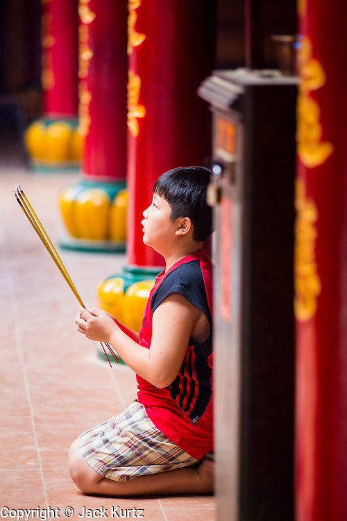 """12 APRIL 2012 - HO CHI MINH CITY, VIETNAM: A boy prays in Quan Am Pagoda. Chùa Quan Âm (Avalokiteshvara Pagoda), a Chinese style Buddhist pagoda in Cho Lon. Founded in the 19th century, it is dedicated to the bodhisattva Quan Âm. The pagoda is very popular among both Vietnamese and Chinese Buddhists. Cholon is the Chinese-influenced section of Ho Chi Minh City (former Saigon). It is the largest """"Chinatown"""" in Vietnam. Cholon consists of the western half of District 5 as well as several adjoining neighborhoods in District 6. The Vietnamese name Cholon literally means """"big"""" (lon) """"market"""" (cho). Incorporated in 1879 as a city 11km from central Saigon. By the 1930s, it had expanded to the city limit of Saigon. On April 27, 1931, French colonial authorities merged the two cities to form Saigon-Cholon. In 1956, """"Cholon"""" was dropped from the name and the city became known as Saigon. During the Vietnam War (called the American War by the Vietnamese), soldiers and deserters from the United States Army maintained a thriving black market in Cholon, trading in various American and especially U.S Army-issue items.         PHOTO BY JACK KURTZ"""