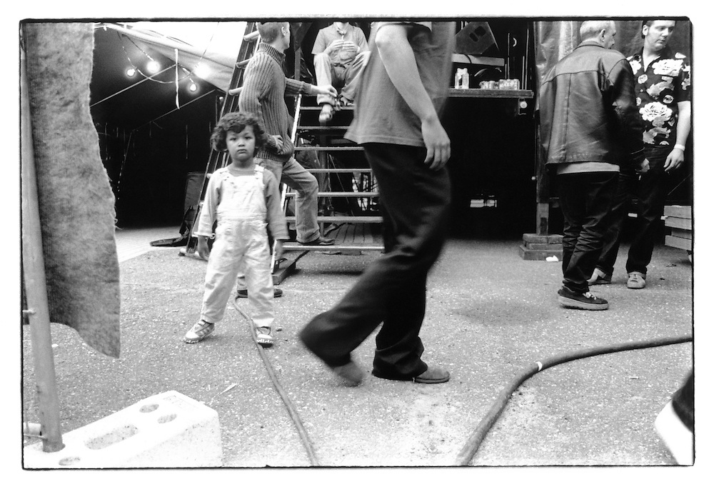 Members of 'The Internationals' and a child backstage before their performance on stage. Turnhout, Belgium, 2003