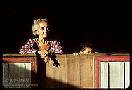 Elderly woman gazes from front porch of her home as grandson peeks out beside her;Eirunepe,AM Brazil