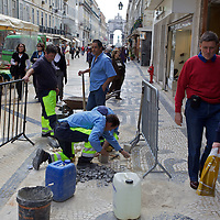 Workers repair some 'Portuguese Pavement' in a busy tourist area of Lisbon.  en.wikipedia.org/wiki/Portuguese_pavement ( http://en.wikipedia.org/wiki/Portuguese_pavement ) . They clearly prioritize the tourist areas...