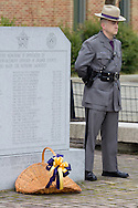 Goshen, New York - A New York State trooper stands by a monument during the Orange County Law Enforcement Officer Memorial Service on May 2, 2014. The memorial service honors the memory of the 27 members of the Orange County law enforcement community that died in the line of duty. The service also pays tribute the families and loved ones left behind for their courage, dignity and perseverance.