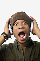 Portrait of a surprised young African American man listening music through headphones