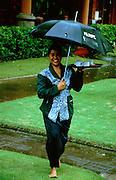 Jimbaran Beach. Waitress with umbrella during a monsoon shower at Keraton Bali Hotel.