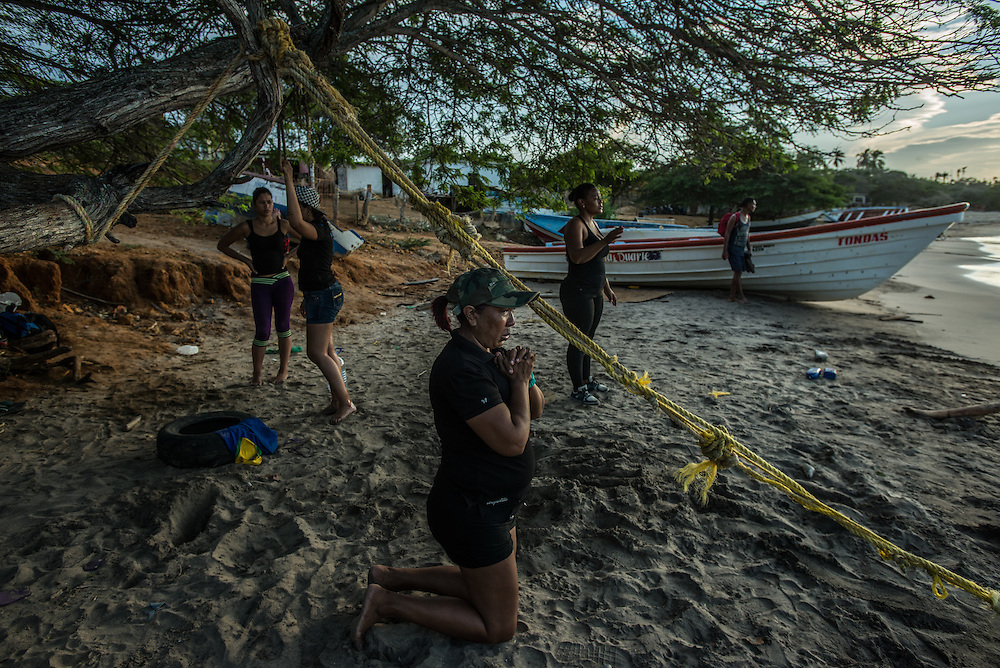 FALCÓN, VENEZUELA - SEPTEMBER 26, 2016: Maria Piñero dropped down on her knees and prays on the beach for safety during their difficult and risky journey, just before boarding the smuggler's boat that will illegally take her and over a dozen other illegal migrants from Venezuela to Curaçao.  Ms. Piñero was very afraid, but was determined to make the trip and make a better life for herself and her family in Curacao.  Undocumented migrants here have mortgaged property, sold kitchen appliances and even borrowed money from the same smuggling rings that pack them on the floorboards alongside drugs and other contraband. The journey to Curaçao takes them on a 60-mile crossing filled with backbreaking swells, gangs of armed boatmen and coast guard vessels looking to capture migrants and send them home. Then, after being tossed overboard and left to swim ashore, they hide in the brush to meet contacts who spirit them anew into the tourist economy of this Caribbean island. They clean the floors of restaurants, work in construction, sell trinkets on the street, or even solicit Dutch tourists for sex. But at least, the migrants say, there is food. PHOTO: Meridith Kohut for The New York Times