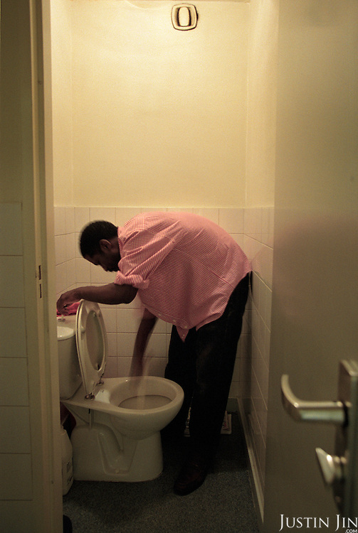 An illegal immigrants from Niger cleans a toilet in Amsterdam central area. The immigrant, Johnny, was a high-school teacher back home. .Picture taken 2002 by Justin Jin. ..