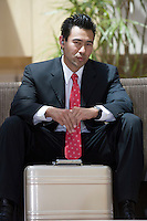 Business man with briefcase indoors, portrait