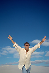 Man in White Sands, NM with outstretched arms as if he is flying