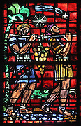 The grapes of the promised land, men carrying a harvest of grapes, lancet window from the South transept, by Jacques Simon, commissioned in 1954 by the Corporation des Vins de Champagne, the lobby of Champagne producers, after damage to the original windows in WWII, in the Cathedrale Notre-Dame de Reims or Reims Cathedral, Reims, Champagne-Ardenne, France. The cathedral was built 1211-75 in French Gothic style with work continuing into the 14th century, and was listed as a UNESCO World Heritage Site in 1991. Picture by Manuel Cohen