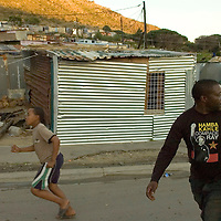 South African Communist Party member and local leader Morris ... walks through Imizamo Yethu shanty town, Hout Bay, Cape Town, South Africa. The work of the CPF and neighbourhood watch have seen the crime rate in Hout Bay drop 63%, but relations between the shanty town of Imizamo Yethu and Hout Bay are tense.  photo  Leonie Marinovich