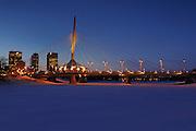 Esplanade Riel Bridge, the Red River and the Winnipeg skyline in winter, dusk, night time<br /> Winnipeg<br /> Manitoba<br /> Canada