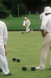 Elderly man bowling on green,