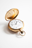 Golden pocket stopwatch over white background