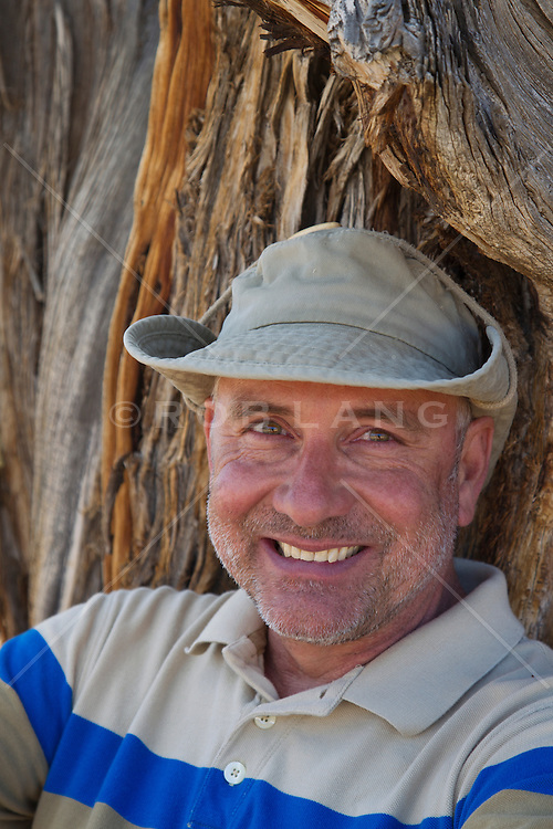 portrait of a handsome man smiling and leaning against a tree