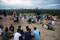 © Licensed to London News Pictures . 27/07/2018. London, UK. People gather on Primrose Hill hoping to catch sight of the blood red moon in total eclipse over London. The rare phenomenon occurs when the Sun, the Earth and the Moon are in perfect alignment and the sun's light is refracted through the Earth's atmosphere whilst the Earth's shadow is cast over the moon . Photo credit: Peter Macdiarmid/LNP