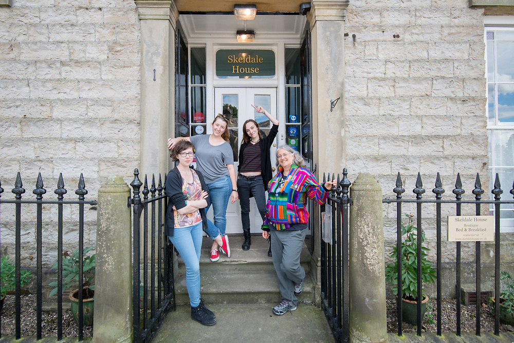 Group of women pose in front of Skeldale House, Yorkshire Dales, UK
