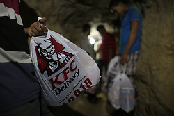 59645973.A man delivers KFC food in the underground tunnel beneath the Gaza-Egypt border in the southern Gaza Strip city of Rafah on May 15, 2013. Ordering fast food from one of the world s most popular restaurants KFC has become possible in Gaza after Al-Yamama delivery company started to bring the food from the Egyptian north Sinai, which borders Gaza, May 15, 2013. Photo by: imago / i-Images. UK ONLY
