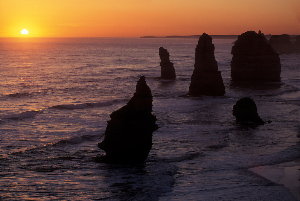 Australia, Victoria, Setting sun over Southern Ocean and Twelve Apostles in Port Campbell National Park